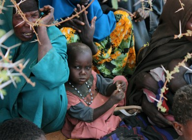 A child sits among the recent arrivals at a refugee camp in Somalia ear;oer tjos ,pmtj/