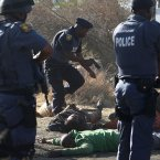 Police surround the bodies of striking miners after opening fire on a crowd  at the Lonmin Platinum Mine near Rustenburg, South Africa. South African police opened fire Thursday on a crowd of striking workers at a platinum mine, leaving an unknown number of people injured and possibly dead. Motionless bodies lay on the ground in pools of blood.  (AP Photo)