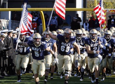 Members of the Navy team heading onto the field before a game last November. Their college football season opener is to take place in Dublin - but potential legal proceedings could put that under threat.