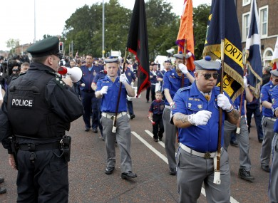 Police calling on a loyalist band to stop as it passed St Patrick's church in Belfast yesterday.