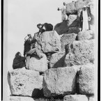A tourist being helped by local men while climbing a pyramid. (Library of Congress, Prints & Photographs Division)