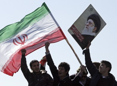 File photo of Iranian youths with the country's flag and poster depicting supreme leader Ayatollah Ali Khamenei
