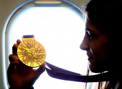 Katie Taylor admires her London 2012 Olympic gold medal shortly before leaving Heathrow to return home last Monday.