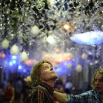 People walk along a street during a local festival in Barcelona's Gracia neighborhood in Spain. (AP Photo/Manu Fernandez)