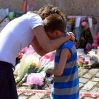A young boy is comforted by his mother after laying flowers near the scene in New Addington, Croydon, after the 12-yea-old's body was discovered. Photo: Gareth Fuller/PA Wire