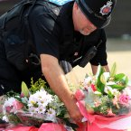 A Police officer lays flowers for local people near the scene in New Addington. Photo: Gareth Fuller/PA Wire