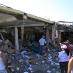 People stand in front of damaged commercial shops after a explosion in the Amuay refinery. (AP Photo/Ariana Cubillos/PA)
