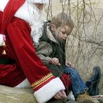 Marty the Meerkat is fed by Santa Claus and three-year-old Luke Kearney in Dublin Zoo in November 2005. (Image: Photocall Ireland)