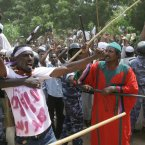 A Sudanese protester chants slogans as a cordon of police try to contain the crowd during a protest in Khartoum.