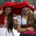 Two women enjoy the beer and rain in Munich this morning. (AP Photo/Matthias Schrader)