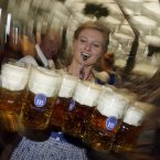 A waitress delivers Masskrugs to the waiting punters this morning. (AP Photo/Matthias Schrader)