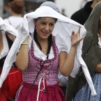 A girl in traditional attire tries to fend off the rain. (AP Photo/Matthias Schrader)