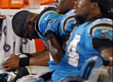Carolina Panthers quarterback Cam Newton lowers his head while sitting on the bench against the New York Giants.