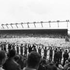 Supporters hold scarves before the pitch filled with flowers at Anfield at a ceremony to remember victims of Hillsborough (Photo: Eric Shaw/PA Archive/Press Association Images)