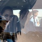 Angelina Jolie, waves through the dusty window of her car as she departs the Zaatari Refugees Camp in Jordan for Syrians who fled the civil war in their country (AP photo/Mohammad Hannon)