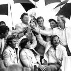 1983: The American team pose under umbrellas with the trophy following their 14.5-13.5 victory over Europe.