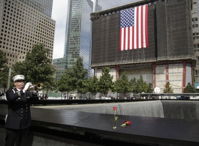 New York City Fire Department captain Tom Engel plays taps during the observance at the World Trade Center Memorial.