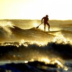 A board surfer enjoys the waves as the sun rises over Tynemouth beach. (PA Photo Owen Humphreys)