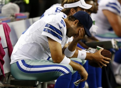 Cowboys quarterback Tony Romo holds his head after throwing the fourth of five interceptions against the Bears.