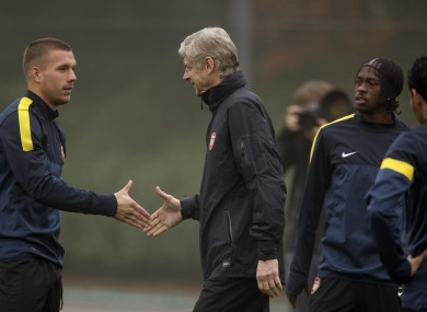 rsenal's Lukas Podolski, left, shakes hands with manager Arsene Wenger.
