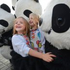Sisters Sally and Sophie Shaw get a cuddle from the giant pandas on Princes Street, Edinburgh. (Mark Runnacles/PA)