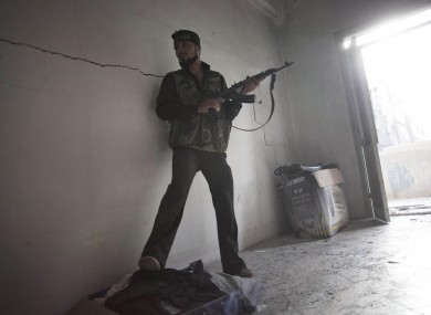 Free Syrian Army soldier takes cover while fighting against Syrian Army troops in Aleppo, Syria, Tuesday, Oct. 2, 2012