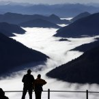 A couple enjoy the view over the clouds of the Alps mountains on a visitor's platform under the top of Wendelstein mountain (1,838 metres) near Bayrischzell, southern Germany. (AP Photo/Matthias Schrader)