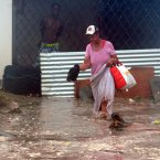 A woman wades through flood water brought by Hurricane Sandy as she evacuates her home in the Caribbean Terrace neighborhood of eastern Kingston, Jamaica,yesterday. 