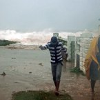 Residents evacuate their home as waves crash in the Caribbean Terrace neighborhood of eastern Kingston, Jamaica, yesterday. 