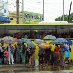 Commuters wait at a bus stop as rain brought by the outer bands of Tropical Storm Sandy falls in Kingston, Jamaica, yesterday. The US National Hurricane Center in Miami said Sandy was expected to become a hurricane as it neared Jamaica on Wednesday. (AP Photo/Collin Reid)