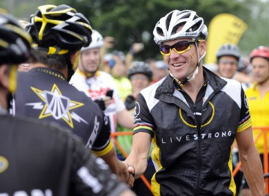 Lance Armstrong greets fellow riders prior to the start of his Livestrong Challenge 10K ride for cancer in 2010.