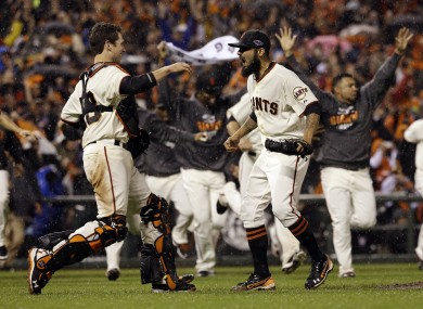 Giants relief pitcher Sergio Romo and catcher Buster Posey react after the final out.