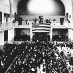 Hundreds of immigrants sit in the Great Hall of Ellis Island on New Year's Day, 1900, as they await processing procedures to begin for their possible entrance into the United States. (AP Photo/National Parks Service, Statue of National Monument)