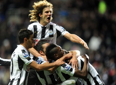 Newcastle United players mob Papiss Cisse after his late goal.