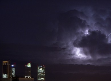 An electrical storm lights up the night sky behind the business district in Madrid, Spain, Wednesday, Oct. 10, 2012.