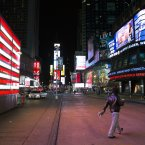 A lone pedestrian walks through an empty Times Square early this morning. (AP Photo/ John Minchillo)