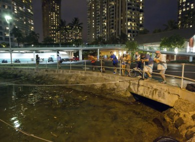 Visitors and Oahu residents watch the water level in the Ala Wai Harbour, while waiting for the arrival of a tsunami a few hours ago. The state's tsunami warning has now been lifted.