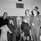 A group of the men picked up in New York hotels, clubs and restaurants by immigration inspectors and city detectives on 9 May, 1941 in a round-up directed at aliens accused of overstaying their leaves in the US, await their transfer from a police station to Ellis Island. (AP Photo)