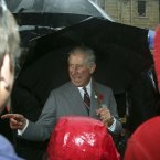The Prince of Wales laughs with well wishers as he braved the inclement weather at Salamanca in Hobart, Australia. Image: AP Photo/Rob Griffith