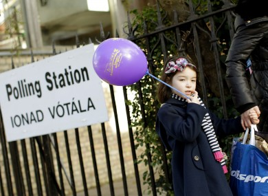 Sinead Yang Yang Glynn, aged four, passes a polling station in Ranelagh, Dublin with her mother Dan Dan Glynn yesterday.