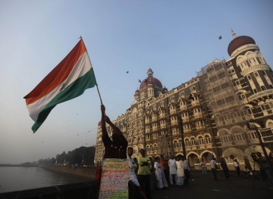 A man waves an Indian flag outside the Taj Mahal hotel, one of the sites of the Mumbai terror attacks