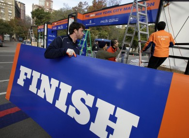 Workers assemble the finish line for the New York City Marathon at Central Park.