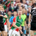 Up, up and away. Mayo's Colm Boyle celebrates a late score as Sligo's Johnny Martin and Ross Donovan watch the flight of the ball. (INPHO/James Crombie).