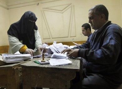 Egyptian referendum officials count votes at a polling station in Cairo after ballots were cast in the referendum on adopting a new constitution.