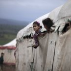 10 December: Syrian girls peek out of their makeshift school at a camp for displaced Syrians in the village of Atmeh. This tent camp sheltering some of the hundreds of thousands of Syrians uprooted by the country's brutal civil war has lost the race against winter: the ground under white tents is soaked in mud, rain water seeps into thin mattresses and volunteer doctors routinely run out of medicine for coughing children. (AP Photo/Muhammed Muheisen)