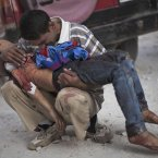 3 October: A Syrian man cries while holding the body of his son killed by the Syrian Army near Dar El Shifa hospital in Aleppo. (AP Photo/ Manu Brabo, File)