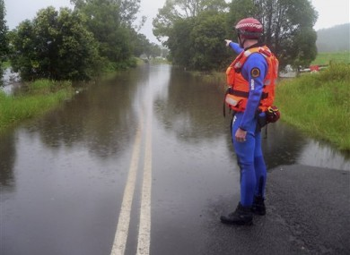A police officer at Bruxner Highway, which is covered with floodwaters caused by torrential rains in northern New South Wales.