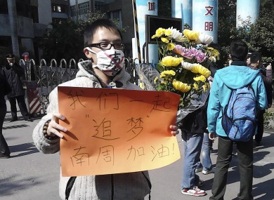 In this photo taken and provided by activist Wu Wei, a man wearing a mask with words