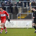 Derry's Dermot McBride gets a yellow card from referee Martin McNally in Omagh. Credit: Russell Pritchard / Presseye