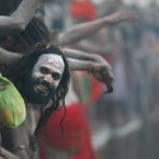 A Naked Hindu holy man or a Naga Sadhu watches others as they wait for a dip at Sangam. (AP Photo /Manish Swarup)